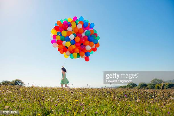 woman running holding big bunch of balloons