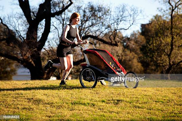 A woman running in a park and pushing a pram