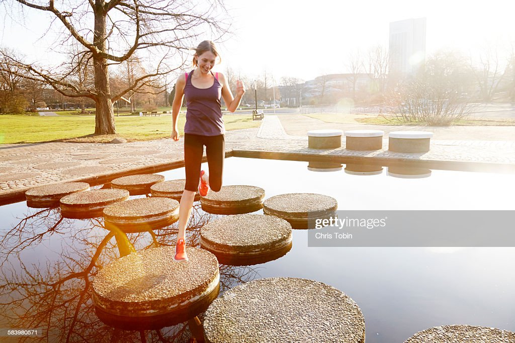 Woman running in city park across stepping stones : Stock Photo