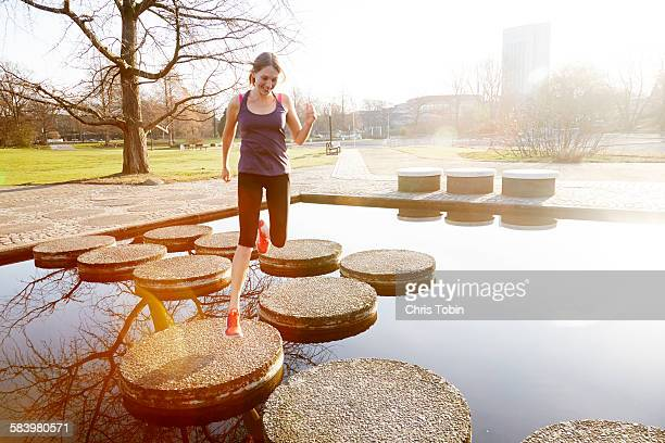 Woman running in city park across stepping stones