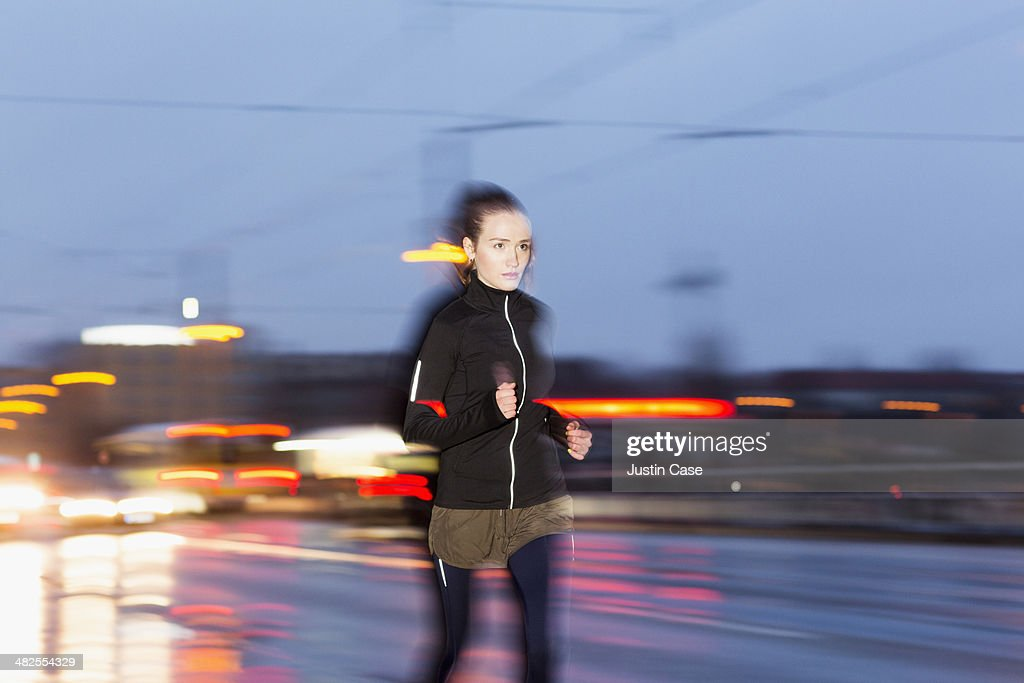 Woman running in fast through city evening : Stock Photo