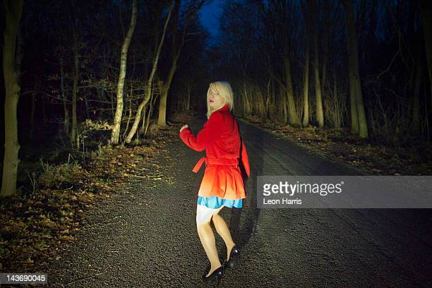 Woman running in fear in woods at night