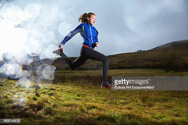 Woman running in grassy field
