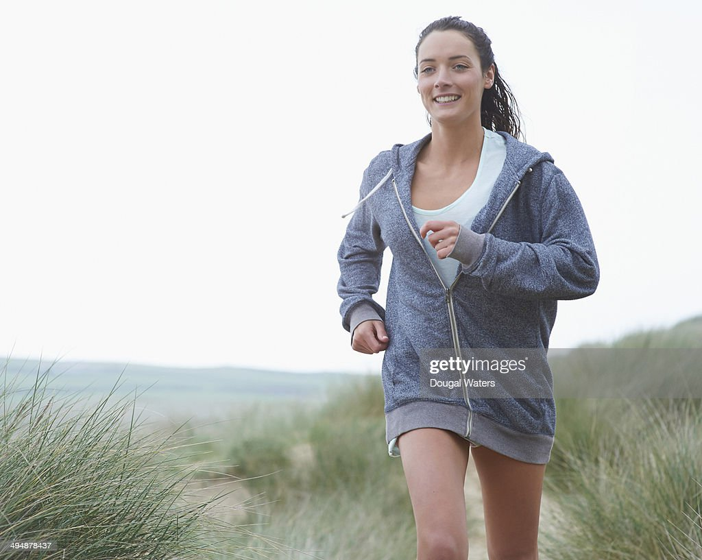 Woman running in sand dunes. : Stock Photo
