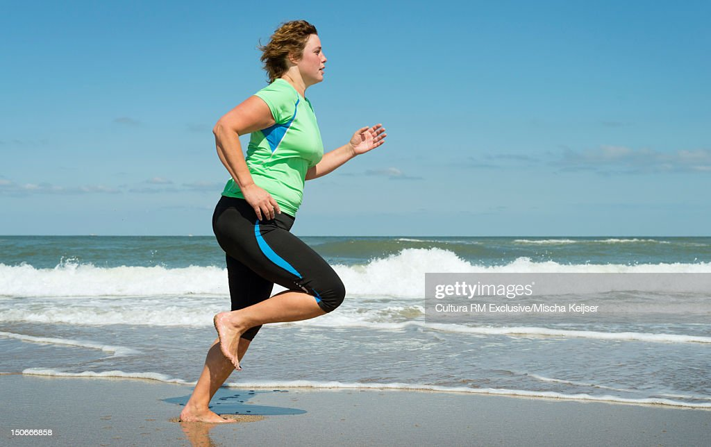 Woman running in waves on beach : Stock Photo