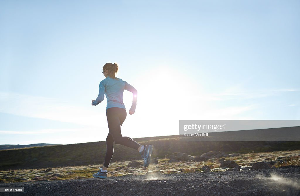 Woman running mountain trail in sunset : Stock Photo