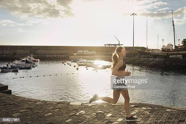 Woman running near harbor at sunset