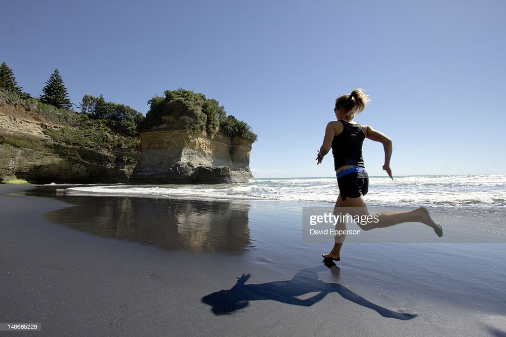 Woman running on a beach in New Zealand : Stock Photo