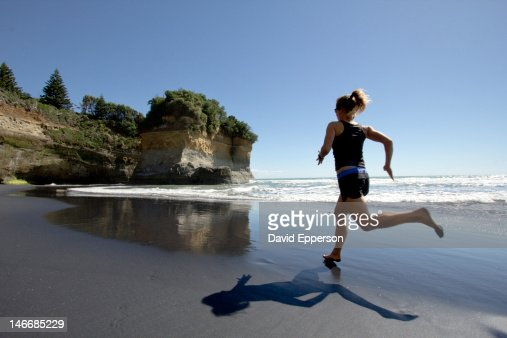 Woman running on a beach in New Zealand : ストックフォト
