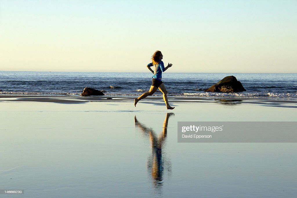 A woman running on a beach in New Zealand