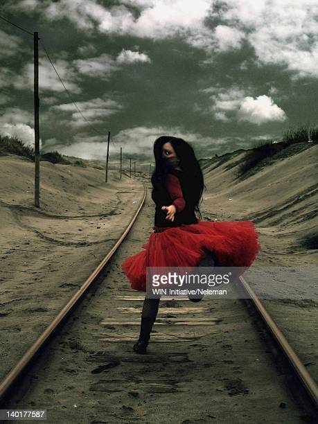 Woman running on a railroad track