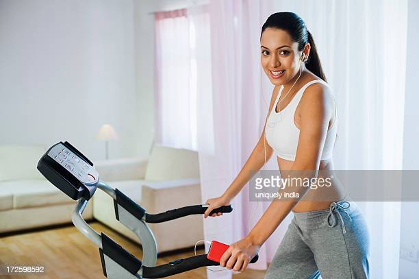 Woman running on a treadmill and listening to music with an MP3 player