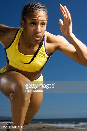 Woman running on beach, close-up : Stock Photo