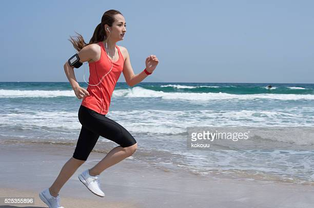 Woman running on beach in order to train leg strength