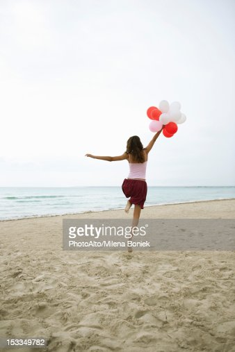 Woman running on beach with bunch of balloons, rear view : Stock Photo