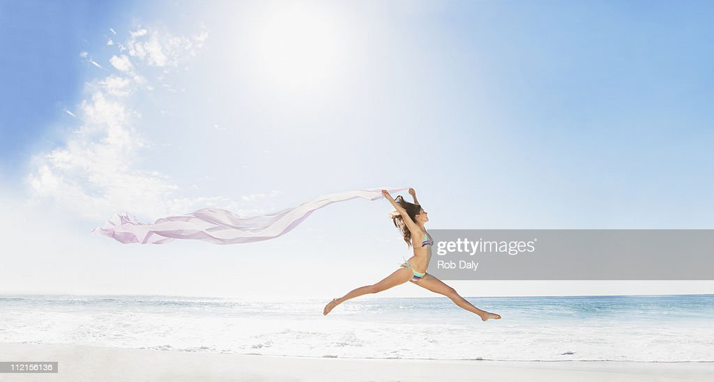 Woman running on beach with fabric : Stock Photo