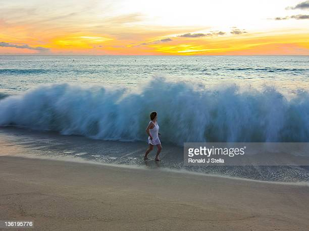 Woman running on beach with huge tide