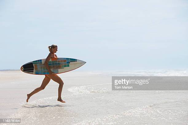 Woman running on beach with surfboard