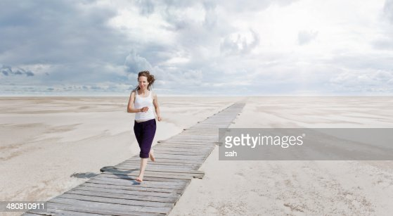 Woman running on boardwalk, Sankt Peter Ordings, Schleswig Holstein, Germany
