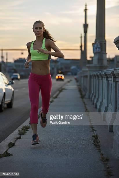 Woman running on city sidewalk