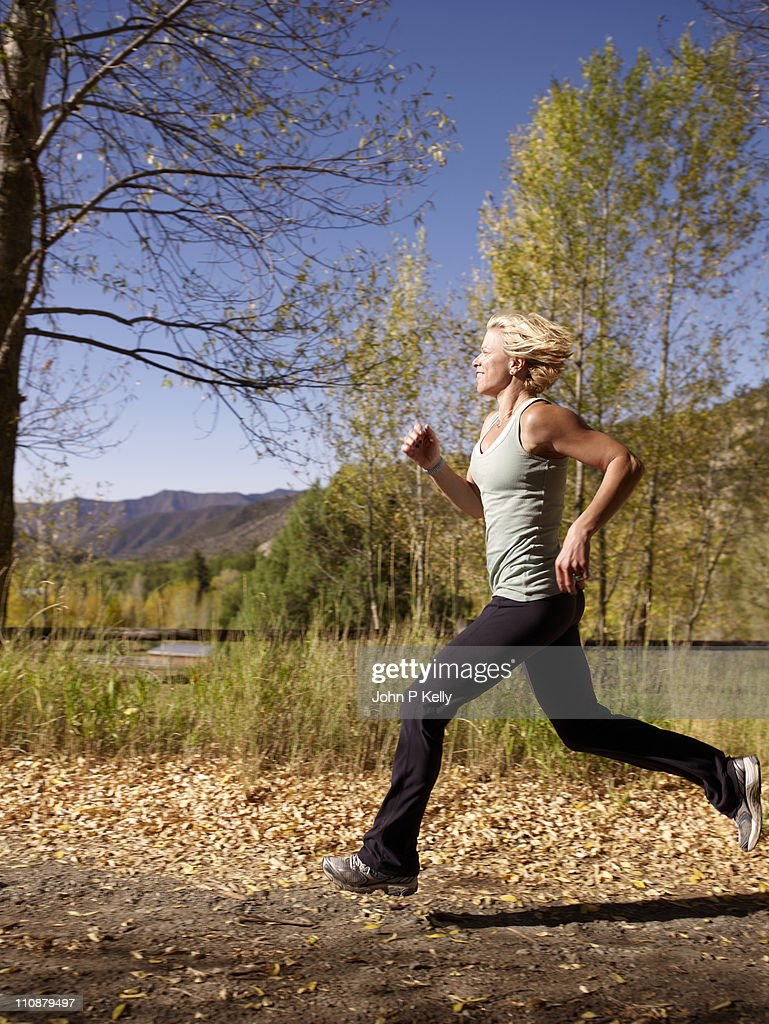 Woman running on dirt trail in countryside : Stock Photo