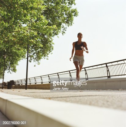 Woman running on embankment, low angle view