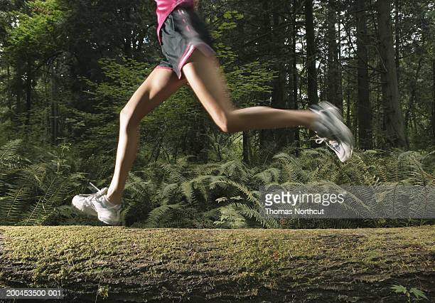 Woman running on log in forest, low section (blurred motion)
