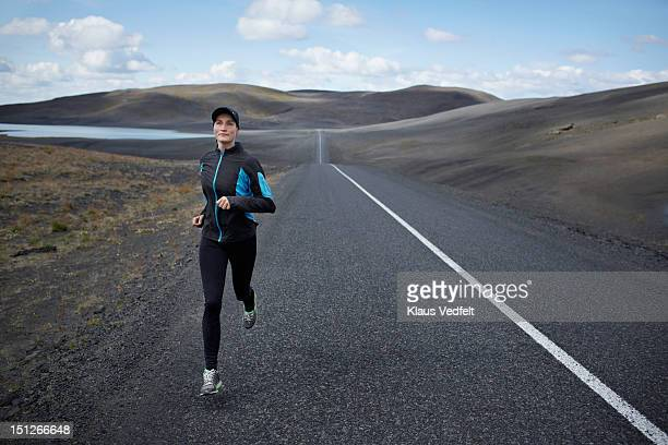 Woman running on long straight road