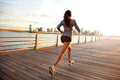 Woman running on pier in front of city skyline