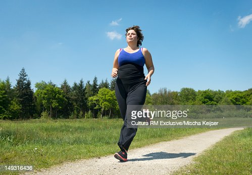 Woman running on rural road : Bildbanksbilder