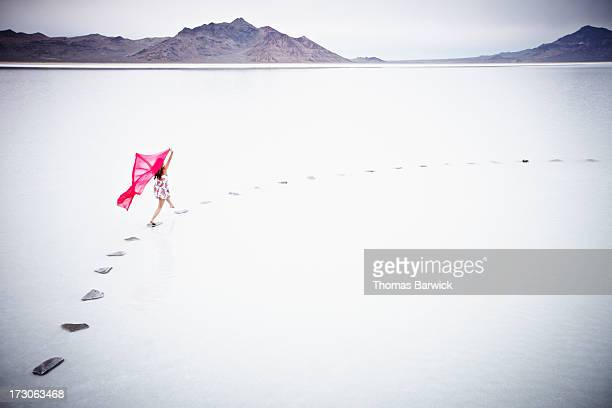 Woman running on stone pathway in lake with scarf
