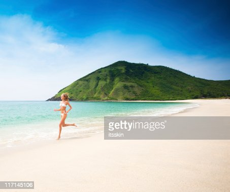 Woman running on the beach : Foto de stock