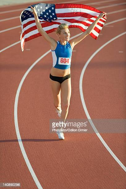 Woman running on track with American flag