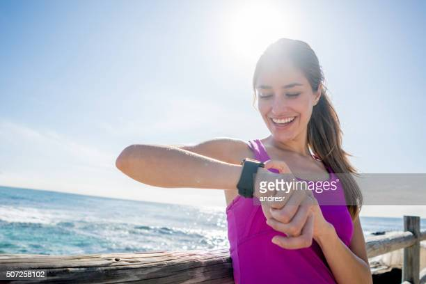 Woman running outdoors using a smart watch