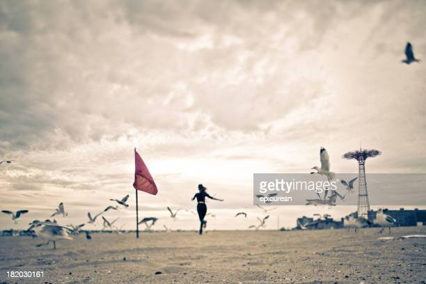 Mulher correr através de um bando de gaivotas