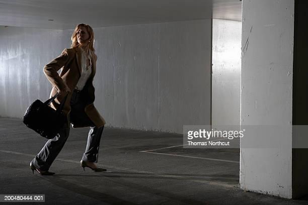 Woman running through dark parking garage, side view