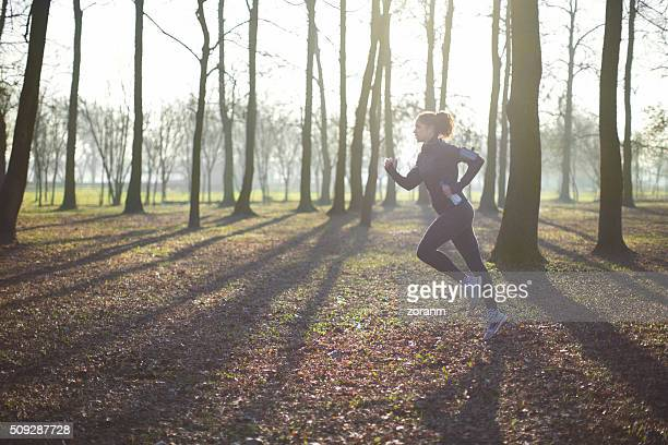 Woman running through forest
