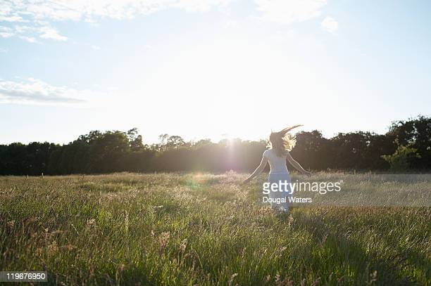 Woman running through grasses in countryside.