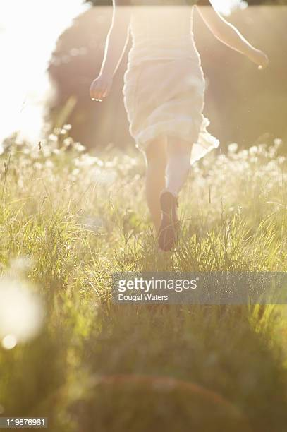 Woman running through meadow.