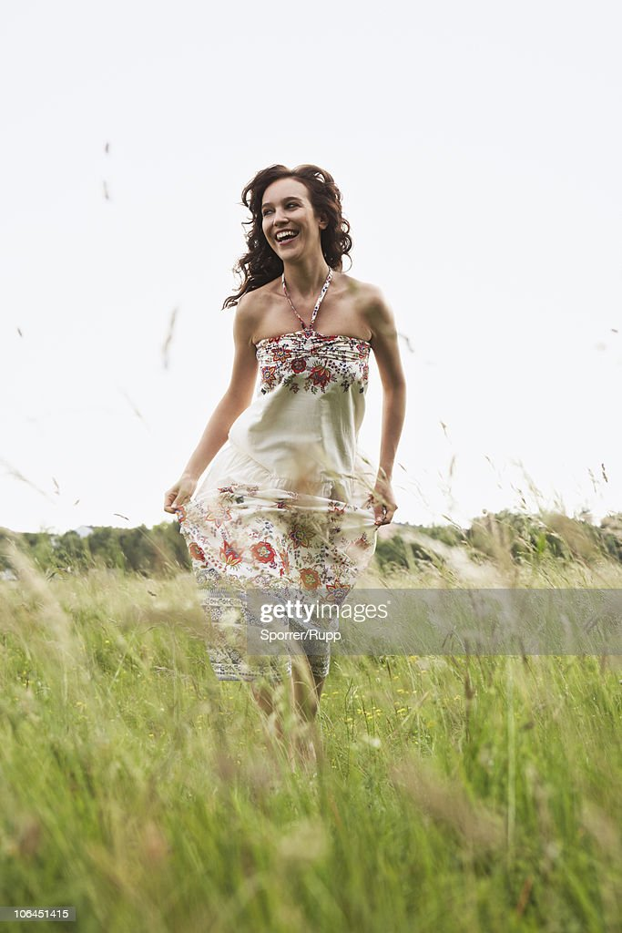 Woman running through wild meadow : Stock Photo