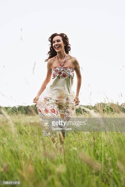 Woman running through wild meadow