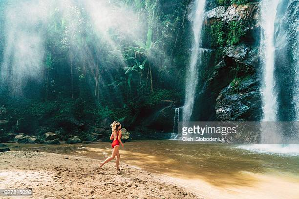 Woman running to tropical waterfall