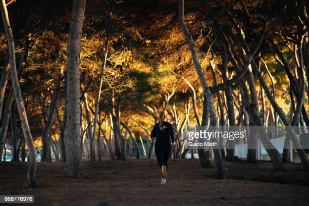 Woman running under trees.