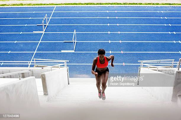 Woman running up stadium stairs