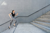 Woman running up steps in urban setting