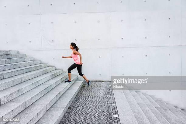 Frau läuft auf der Treppe im der urbanen Ambiente