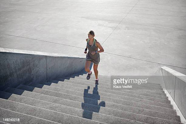 Woman running up steps in urban setting, rear view