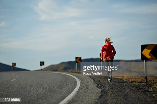Woman running uphill on big road,mountains in back : Stock Photo