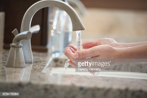 Woman running water on hands : Stockfoto