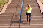 Full length rear view of an active and determined middle-aged woman running while climbing stairs during intense workout for weight loss outdoors in a sunny day